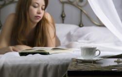 Jeune beau livre de lecture sexy de femme sur un lit dans la chambre d'hôtel photographie stock
