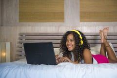 Jeune beau mensonge afro-américain noir heureux de chambre à coucher de femme à la maison gai sur le lit écoutant la musique d'In photo stock
