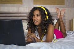 Jeune beau mensonge afro-américain noir heureux de chambre à coucher de femme à la maison gai sur le lit écoutant la musique d'In image libre de droits