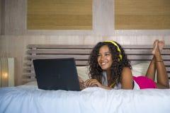 Jeune beau mensonge latino-américain noir heureux de chambre à coucher de femme à la maison gai sur le lit écoutant la musique d' photo libre de droits