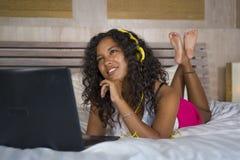 Jeune beau mensonge latino-américain noir heureux de chambre à coucher de femme à la maison gai sur le lit écoutant la musique d' photos libres de droits