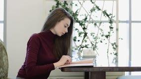 Jeune, beau menu de lecture de femme en café banque de vidéos