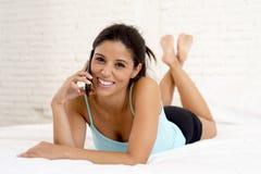 Jeune beau parler hispanique de femme décontracté au téléphone portable dans le lit Image libre de droits
