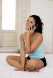 Jeune beau parler hispanique de femme décontracté au téléphone portable dans le lit Photographie stock
