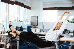 Jeune beau repos réussi de femme d'affaires, détendant sur le lieu de travail, au-dessus du fond de bureau Images libres de droits