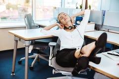 Jeune beau repos réussi de femme d'affaires, détendant sur le lieu de travail, au-dessus du fond de bureau Photographie stock libre de droits