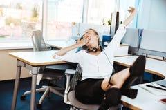 Jeune beau repos réussi de femme d'affaires, détendant sur le lieu de travail, fond de bureau Image libre de droits