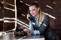 Jeune beau secrétaire de fille souriant et parlant au téléphone dans le bureau Photos stock
