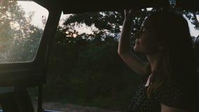 Jeune beau touriste féminin heureux souriant, appréciant le tour atmosphérique de safari en voiture d'excursion le long de forêt  banque de vidéos