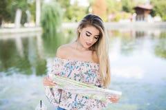 Jeune beau voyageur féminin se tenant sur la ville de rue et regardant la carte Photo libre de droits