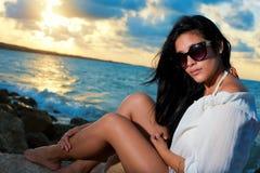 Jeune beauté avec des lunettes de soleil se reposant sur une roche par l'océan Photographie stock libre de droits