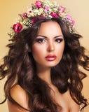 Jeune beauté avec la guirlande des fleurs. Poils parfaits de Brown. Luxe photo stock