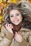 Jeune beauté se trouvant sur des lames en automne Photographie stock libre de droits