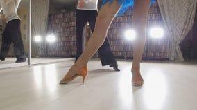 Jeune beaux homme et femme dansant et préparant la danse latino-américaine dans des costumes dans le studio, foyer sur des pieds Photographie stock libre de droits