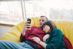 Jeune beaux homme et fille se reposant dans une chambre avec un intérieur moderne et à l'aide d'un téléphone portable Images libres de droits