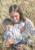Jeune beaux mère et bébé garçon étreignant dans le domaine de blé Image libre de droits