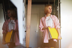 Jeune bel étudiant blond se tenant en son appartement moderne avec un grand dossier avec des documents Images stock