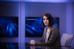 Jeune bel annonceur de télévision de brune au studio pendant la radiodiffusion vivante Directeur féminin de TV au rédacteur dans  photos libres de droits