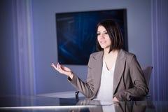Jeune bel annonceur de télévision de brune au studio pendant la radiodiffusion vivante Directeur féminin de TV au rédacteur dans  Photo stock