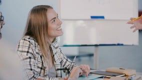 Jeune bel assistant féminin européen de sourire de bureau écoutant le patron féminin de société parlant lors de la réunion banque de vidéos
