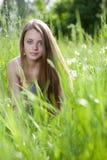 Jeune bel emplacement de fille dans l'herbe Photos stock