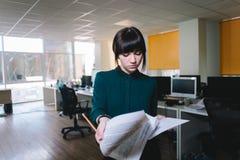 Jeune bel employé de bureau de fille avec une expression sérieuse examinant des documents d'entreprise Photo libre de droits