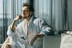 Jeune, bel homme pendant le matin pensant tout en se reposant dans un r photo libre de droits