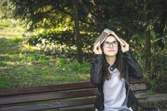 Jeune belle école ou étudiante avec des verres d'oeil se reposant sur le banc en parc faisant la pause de lire les livres et photos stock