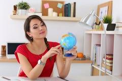Jeune belle étudiante dirigeant quelque chose sur le globe Photos stock