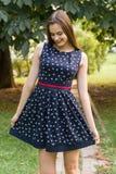 Jeune, belle, attirante femme dans une robe élégante, posant sur l'appareil-photo Elle rit, pose pour l'appareil-photo, ses cheve Photographie stock