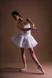 Jeune belle ballerine de femme dans le tutu posant au-dessus du beige Photos stock