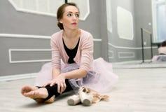 Jeune belle ballerine gracieuse se reposant dans le sitti de classe de ballet Photographie stock