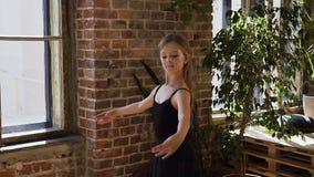 Jeune belle ballerine habillée dans des trains noirs de tutu avec élégance dans des chaussures de ballet de pointe dans la salle  clips vidéos