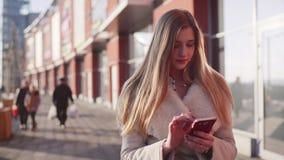 Jeune belle blonde descendant la rue passante près d'un bâtiment moderne au centre de la ville tout en textotant à son téléphone clips vidéos
