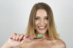 Jeune belle brosse à dents de sourire de participation de femme avec la pâte dentifrice là-dessus étroit vers le haut du fond bla images stock