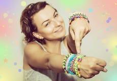 Jeune belle brune avec les bracelets en caoutchouc colorés sur son h Photos libres de droits