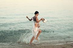 Jeune belle course de dame sur la plage de mer ou d'océan dans l'éclaboussure de l'eau Concept de liberté La femme porte des chau photo stock