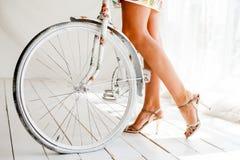 Jeune belle, d'une manière élégante habillée femme avec la bicyclette Images stock