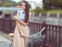 Jeune belle, d'une manière élégante habillée femme avec la bicyclette extérieure photo libre de droits