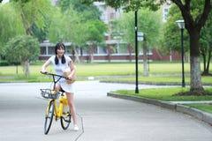 Jeune belle, d'une manière élégante habillée femme chinoise asiatique avec partager la bicyclette Beauté, mode et mode de vie photos stock