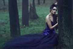 Jeune belle dame dans la robe de soirée luxueuse de paillette se reposant dans les bois brumeux mystérieux se penchant sur l'arbr images libres de droits