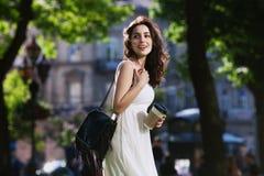 Jeune belle dame de sourire heureuse marchant sur la rue, tenant la tasse de café de papier Vêtements élégants de port modèles et Photos stock