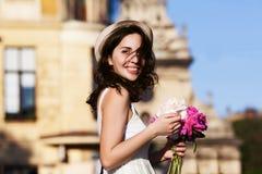 Jeune belle dame de sourire heureuse marchant sur la rue Vêtements et accessoires blancs élégants de port modèles vieux Images libres de droits
