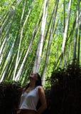 Jeune belle dame posant devant l'appareil-photo avec la forêt en bambou d'Arashiyama sur le fond, Kyoto, Japon Photographie stock libre de droits