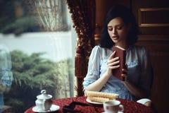 Jeune belle dame s'asseyant à la table dans le café confortable gentil avec le livre dans des ses mains photo libre de droits