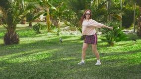Jeune belle danse rousse de fille en parc femme dans une mini danse de jupe en parc tropical sur un fond de clips vidéos