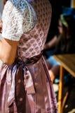Jeune belle demoiselle d'honneur dans une robe traditionnelle de dirndl attendant avec intérêt le mariage photographie stock libre de droits