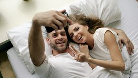 Jeune belle et affectueuse photo de selfie de prise de couples sur l'appareil-photo de smartphone se situant dans le lit au matin Photo stock