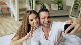 Jeune belle et affectueuse photo de selfie de prise de couples sur l'appareil-photo de smartphone tout en se reposant dans le lit Images libres de droits