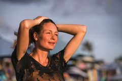 Jeune belle et fascinante femme blonde heureuse posant aussi à la plage portant le sentiment gai de sourire de robe élégante frai photographie stock